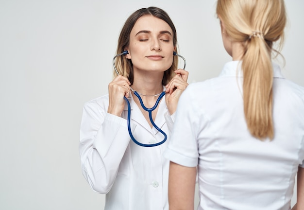 Infermiera in stetoscopio abito medico e vista posteriore del paziente
