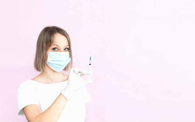 Infermiera in maschera medica e guanti che tengono la siringa su sfondo rosa chiaro con spazio per le copie