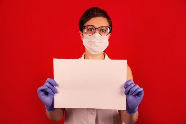 Un'infermiera in una maschera protettiva medica detiene un foglio bianco bianco.