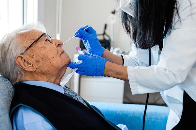Infermiera che esegue il test covid su una persona anziana a casa