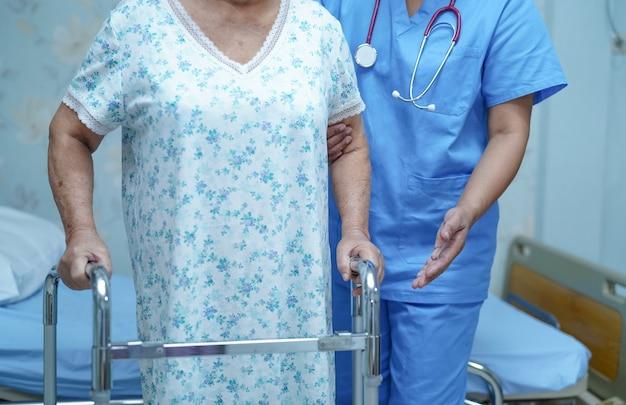 Infermiera fisioterapista cura del medico, aiuto e supporto donna senior paziente a piedi con walker in ospedale.