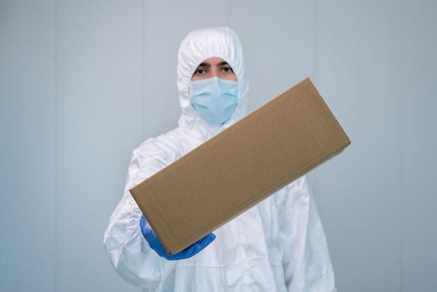Un'infermiera in tuta protettiva mostra una scatola con una mano in un ospedale. l'operatore sanitario riceve forniture mediche per combattere il coronavirus