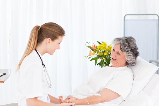 Infermiera che mette una flebo sul braccio del suo paziente