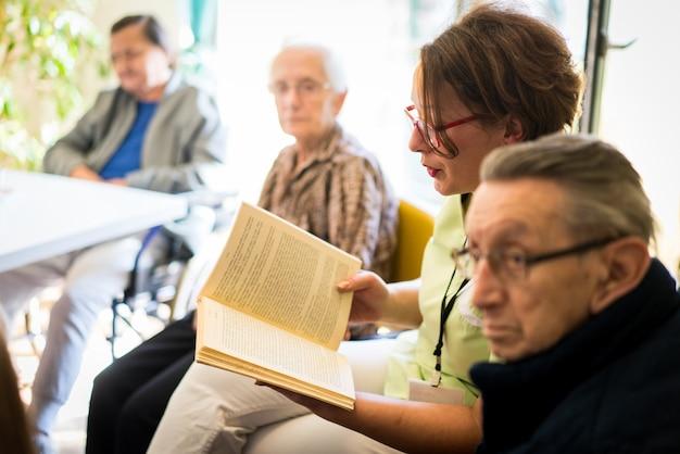 Infermiera lettura libro per anziani gruppo di persone