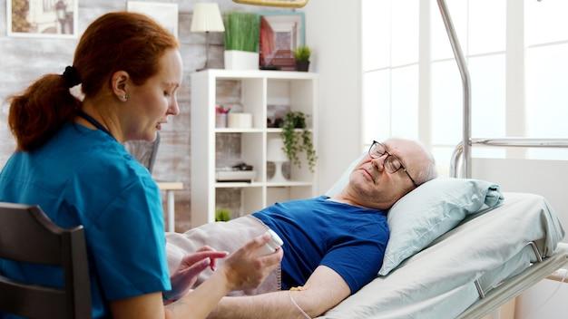 Infermiera in casa di riposo che dà pillole di prescrizione a un uomo malato che giace nel letto d'ospedale. scatto rivelatore su una grande stanza luminosa con grandi finestre