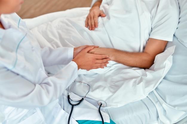 Un'infermiera si siede vicino a un paziente maschio maturo e gli tiene la mano per mostrare la sua cura e il suo sostegno in un moderno reparto ospedaliero.