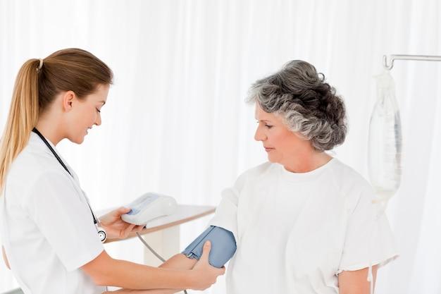 Infermiera che prende la pressione sanguigna del suo paziente