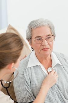 Infermiera che prende il battito cardiaco del suo paziente