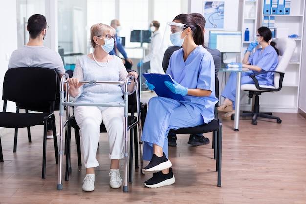 Infermiera che indossa una visiera protettiva contro il coronavirus che parla con un paziente anziano con deambulatore nel corridoio dell'ospedale sul trattamento di recupero