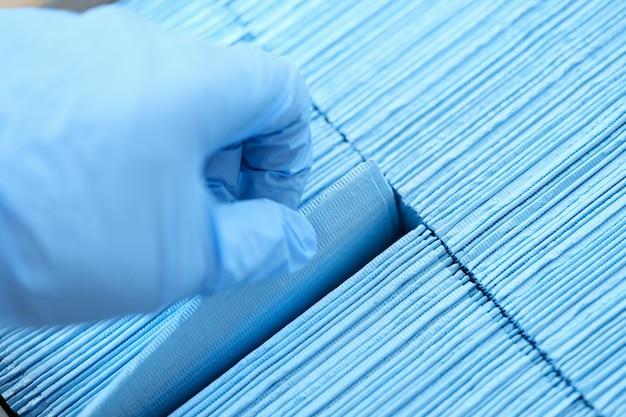 Infermiera che indossa guanti di gomma protettivi che estrae il primo piano medico sterile blu del tovagliolo