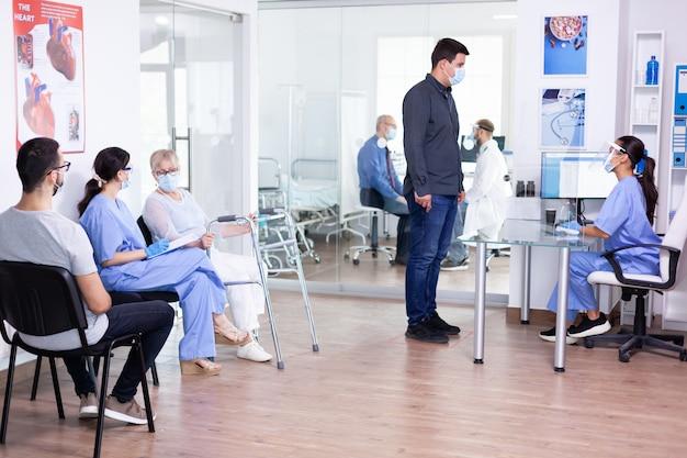 Infermiera che indossa la visiera contro il covid-19 durante la reception dell'ospedale rispondendo alle domande dell'uomo sulla prevenzione del coronavirus