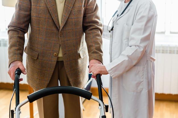Infermiera in camice bianco che tiene la mano di un uomo anziano con un deambulatore al chiuso