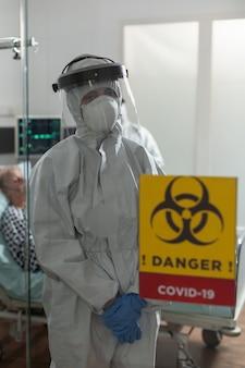 Infermiera con maschera facciale e tuta nella stanza d'ospedale, con l'aria stanca alla telecamera, durante l'epidemia di coronavirus, per prevenire l'infezione