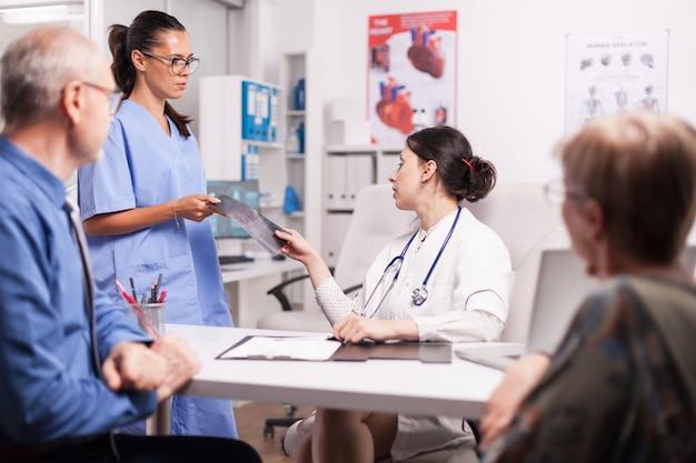 Infermiera con gli occhiali che fa i raggi x al medico durante la consultazione dei pensionati sposati malati nell'ufficio dell'ospedale. giovane medico che indossa camice bianco e stetoscopio.