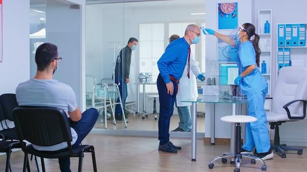 Infermiera con visiera contro il coronavirus nell'area di attesa dell'ospedale che scansiona la fronte dell'uomo anziano per la temperatura utilizzando un termometro a infrarossi. medico con paziente nell'armadietto. donna invalida in sedia a rotelle.