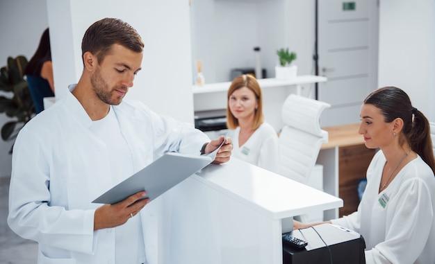 Infermieri e medico in ospedale in uniforme bianca. guy legge il documento.