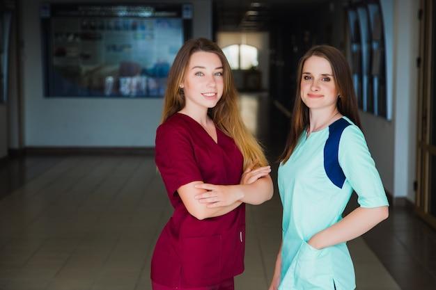 Scuola per infermieri. due degli studenti di medicina professionisti in camice. medici chirurghi del personale. medicina e concetto di assistenza sanitaria