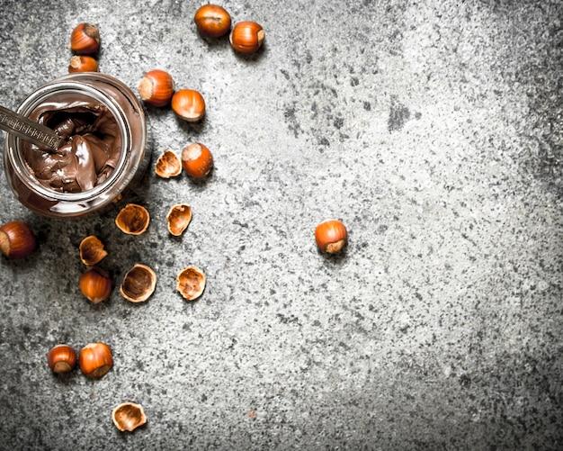 Burro di noci di nocciole e cioccolato su fondo rustico