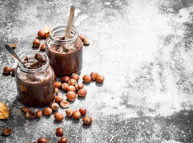 Burro di noci di nocciole e cioccolato. su fondo rustico.