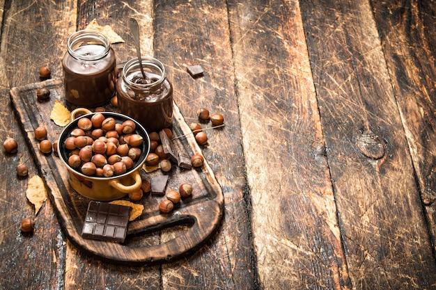 Burro di noci con cioccolato e nocciole su fondo in legno