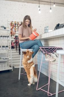 Nutrizione per cani. ragazza che sceglie il cibo per il suo animale domestico in un negozio di animali
