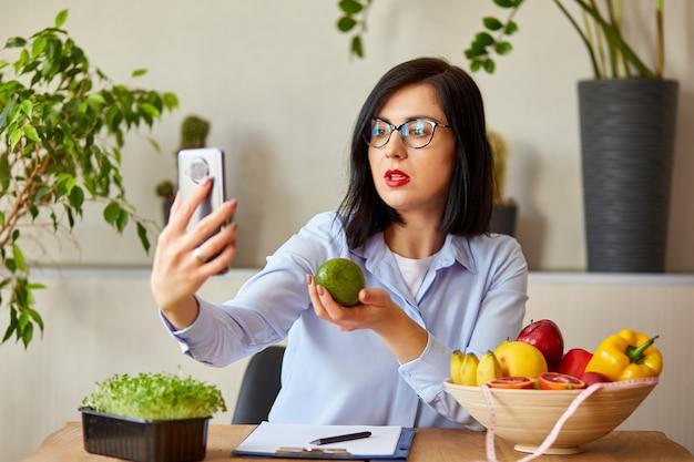 Nutrizionista, dietista che registra su uno smartphone il suo vlog sul concetto di alimentazione sana, assistenza sanitaria e dieta. nutrizionista femminile con frutta che lavora al suo des a casa.