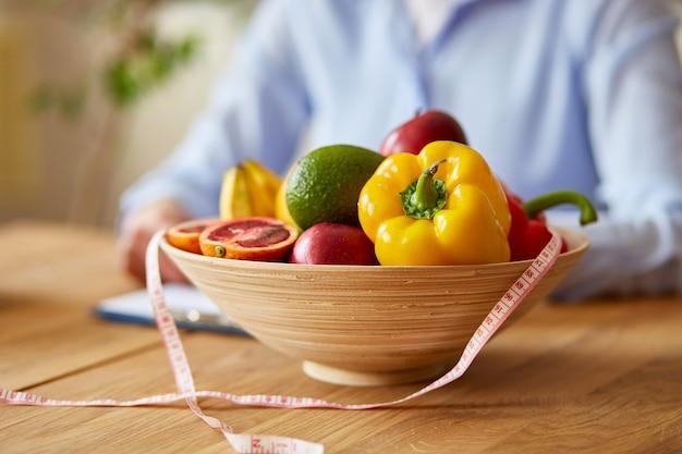 Nutrizionista, dietista che scrive un programma di dieta, con verdure e frutta sane, concetto di assistenza sanitaria e dieta. nutrizionista femminile con frutta che lavora alla sua scrivania.