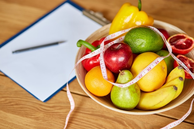 Posto di lavoro dietista nutrizionista con spazio in bianco per nastro di misurazione penna piano dieta e ciotola con frutta e verdura sane sanità e dieta giusta nutrizione e concetto di benessere dimagrante
