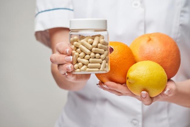 Concetto di stile di vita sano medico nutrizionista - azienda agrumi freschi biologici - pompelmo, arancia, limone e lattina di capsule di vitamina