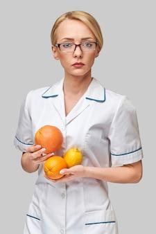 Concetto di stile di vita sano medico nutrizionista - azienda agrumi freschi biologici - pompelmo, arancia e limone