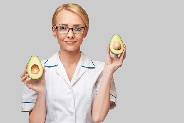 Concetto di stile di vita sano medico nutrizionista - tenendo il frutto di avocado biologico