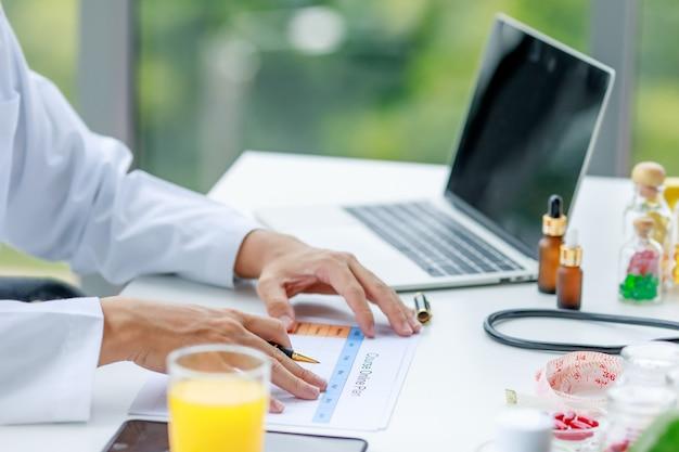 Medico nutrizionista che indossa camice bianco da laboratorio che scrive piano alimentare settimanale per il paziente. frutta e nutrimenti e laptop sul tavolo.