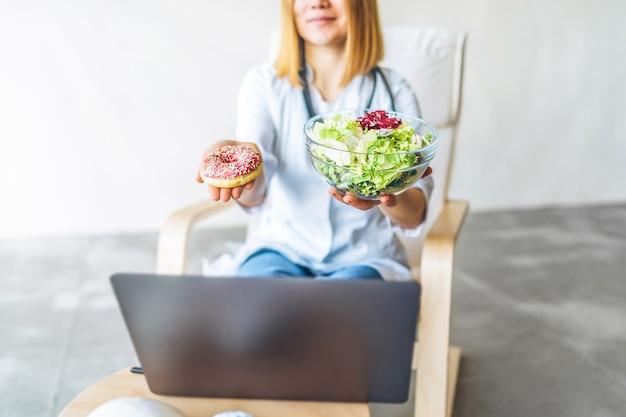 Medico femminile nutrizionista che tiene cibo sano e cibo spazzatura nelle mani, concetto di dieta.