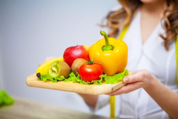 Nutrizionista che tiene frutta e verdure fresche per la dieta sana