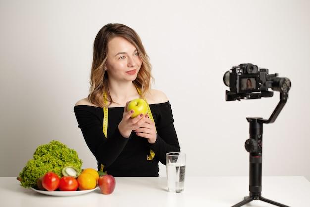 Nutrizionista registra un video blog su un'alimentazione sana su un telefono cellulare.
