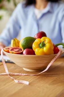 Donna nutrizionista che scrive un programma di dieta, con frutta e verdura sane