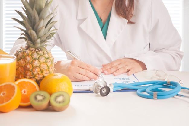 Nutrizionista che scrive cartelle cliniche e prescrizioni con frutta fresca