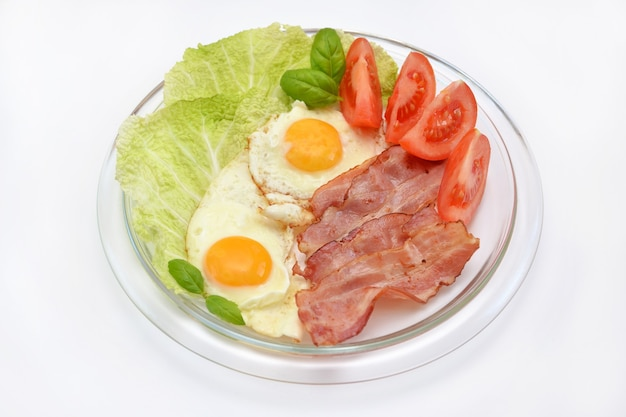 Colazione nutriente uova strapazzate con pancetta e verdure su un piatto
