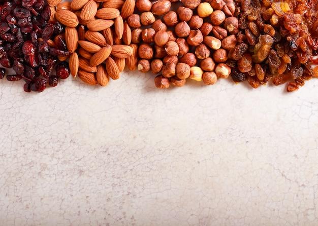 Frutta a guscio (mandorle e nocciole), mirtillo rosso e uva passa sul tavolo di marmo