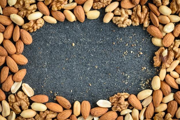 Sfondo di noci di mandorle, arachidi e noci con briciole su sfondo nero.