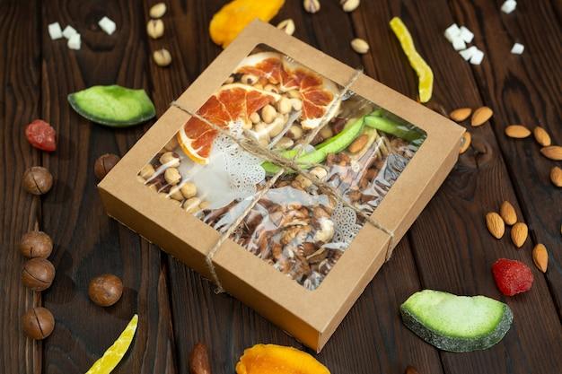 Frutta candita con noci e frutta secca di diverse varietà in una scatola di carta su una struttura in legno