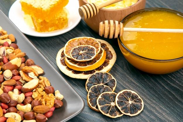 Noci, agrumi secchi e miele di favo fresco. cibo biologico vitaminico