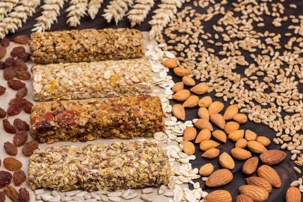 Frutta a guscio, semi, cereali. barretta di muesli proteica bilanciata. spuntino vegano. vista dall'alto. superficie in legno. avvicinamento
