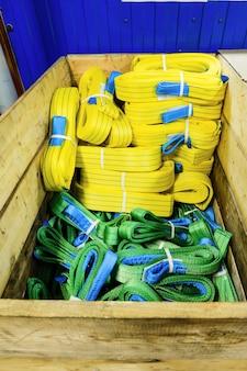 Imbracature di sollevamento morbide in nylon impilate in una scatola di legno. magazzino prodotti finiti per imprese industriali