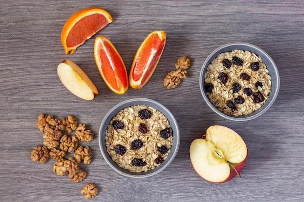 Fiocchi di avena con uvetta, noci, fette di mele e arance, vista dall'alto su un tavolo di legno.