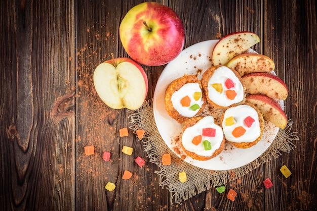 Muffin d'avena con yogurt, frutta candita, mela rossa e cannella su uno spazio di legno scuro.