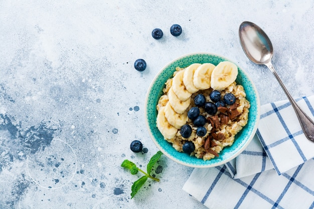 Porridge di avena con banana, cioccolato e mirtillo fresco in una ciotola su una superficie di ardesia, pietra o cemento grigio chiaro