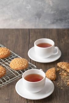 Biscotti di farina d'avena e tazze di tè caldo sulla tavola di legno