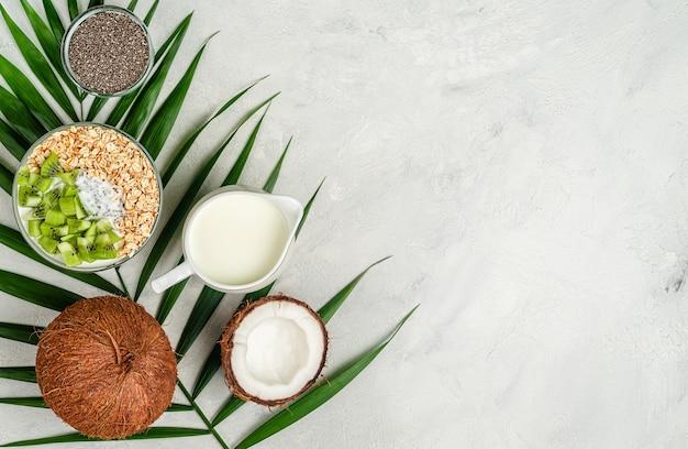 Ciotola di farina d'avena con latte di cocco, semi di chia e kiwi su una superficie di cemento grigio. copia spazio, vista dall'alto