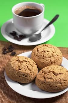 Biscotti di farina d'avena nel piatto e tazza di caffè caldo sul tavolo